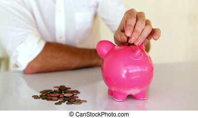 Businessman putting coins into piggy bank in his office
