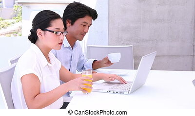 Asian couple using laptop together in the morning outside on...