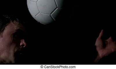 Footballer heading the ball on black background in slow...
