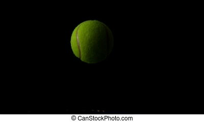 Tennis ball bouncing on a racket in slow motion