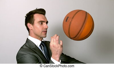 Businessman spinning basketball on finger in slow motion