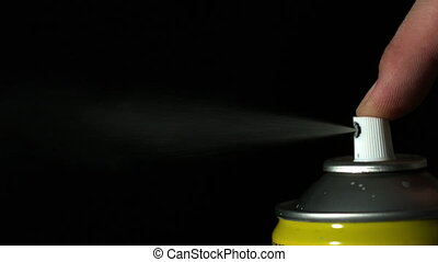 Finger pressing down on aerosol spray in slow motion