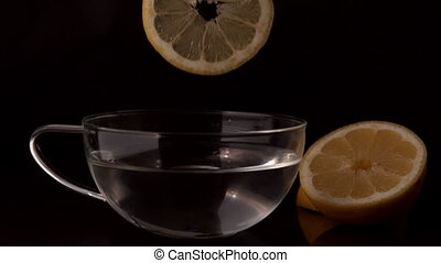 Lemon slices falling into glass cup of water in slow motion