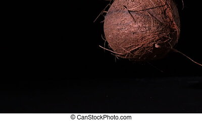 Coconut falling on black surface in slow motion