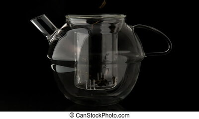 Loose tea pouring into glass teapot in slow motion