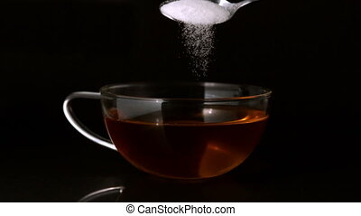Teaspoon pouring sugar into cup of tea in slow motion