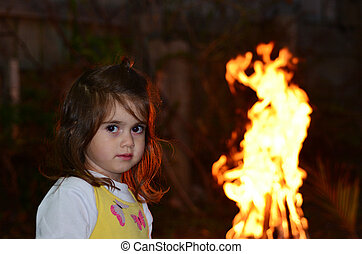 Little girl celebrate Lag Ba'Omer Jewish Holiday by lit a...