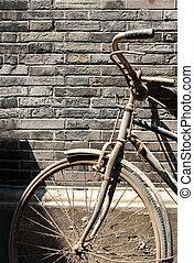 Old Chinese bike against brick wall - Old bike leaning...