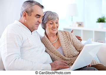 Online shopping - Senior couple surfing the net