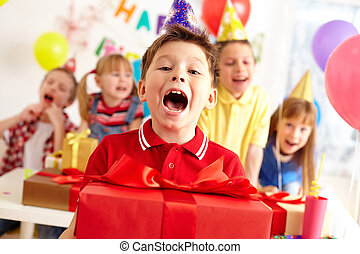 Joyful boy with big red giftbox looking at camera with his...