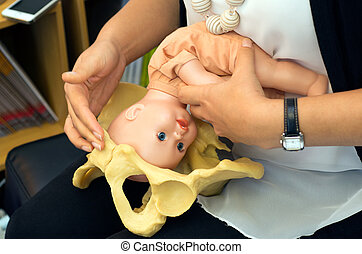 Midwife demonstrate natural childbirth to a pregnant woman -...