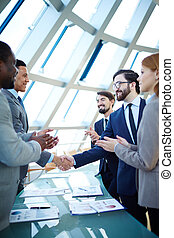 Business agreement - Group of business people congratulating...