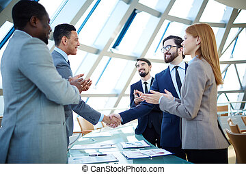 After negotiations - Group of business people congratulating...