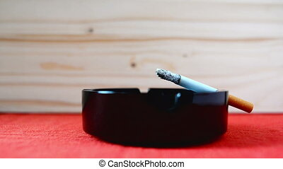 Cigarette burning in black ashtray on the table. 1920x1080,...