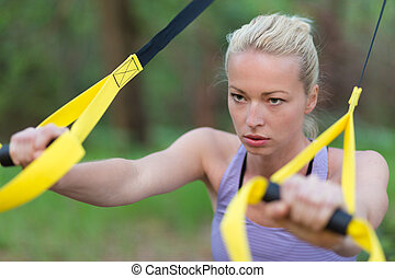 Training with fitness straps outdoors - Young attractive...