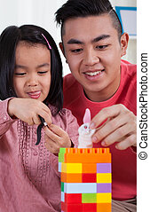 Girl with her brother playing toy blocks and puppets