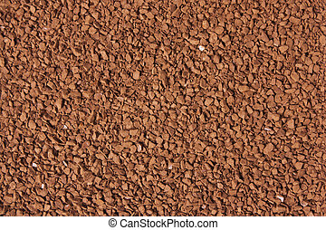 Freeze dried coffee granules spread over a flat surface.