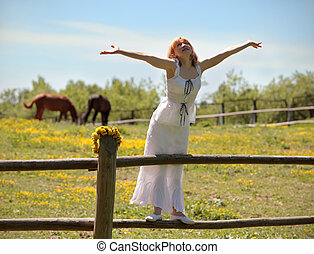 optimism - The girl in a white dress standing on a fence