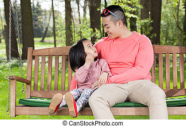 Asian family sitting on a swing, horizontal