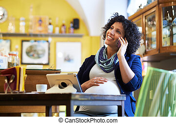 pregnant woman drinking espresso coffee in bar