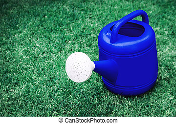 blue watering plastic pot on a green grass field in space in...