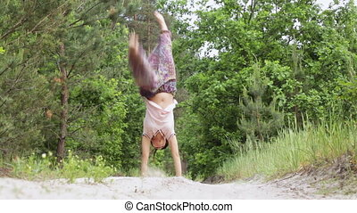 Gymnastics in nature - Girl on nature does a handstand...