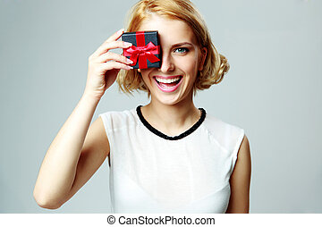 Laughing young woman closing eye with jewelery gift box