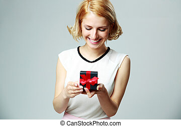 Smiling beautiful young woman holding an open jewelery gift...