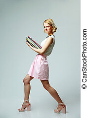 Studio shot of a young woman with notebooks on gray background