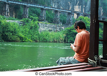 man - Man sitting on the litter at the bridge of the River...