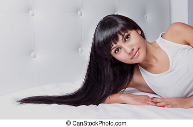 woman in bed - beautiful young brunette woman with long hair...