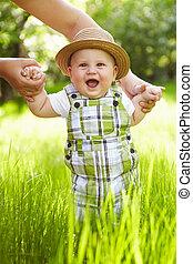 Little boy in the garden. Walking outdoors.