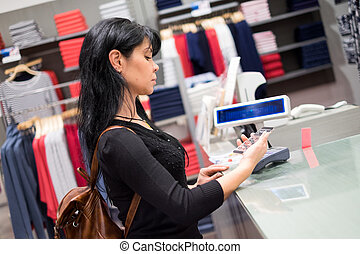 Mobile payment Girl pays to shop using mobile phone - Girl...