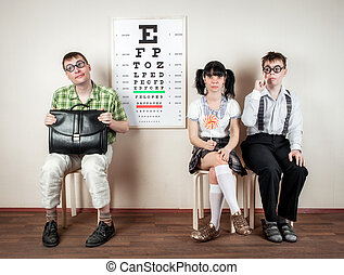 Three person wearing spectacles in an office at the doctor -...