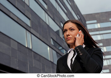 Beautiful business woman on the phone at modern building -...