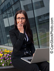 Frightened and stressed beautiful business woman biting her...