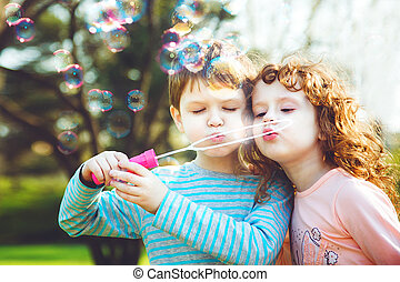 little girl and boy blowing soap bubbles.