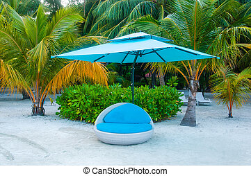 Blue relax SUN chair bed on sand covered with umbrella -...