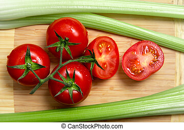 High angle view of bunch of fresh tomatoes and celery sticks...