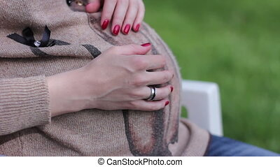 Pregnant girl gently stroking her belly