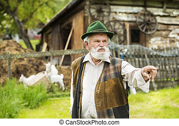 Old farmer with beard and hat standing in backyard garden by...