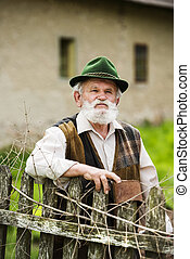 Old farmer with beard and hat standing by the lath fence...