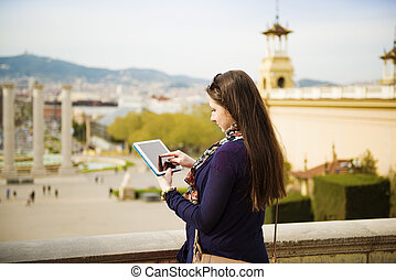Woman tourist - Pretty young female tourist using digital...