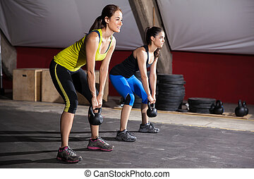 Working out with kettlebells - Two young women working out...