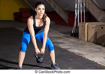 Exercising with a kettlebell - Portrait of a beautiful...