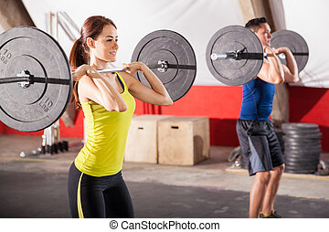 Doing squats at a gym - Cute brunette and a guy doing some...
