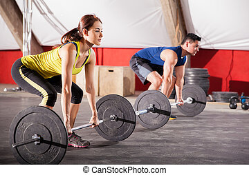 Lifting weights at a gym - Two Hispanic people lifting...