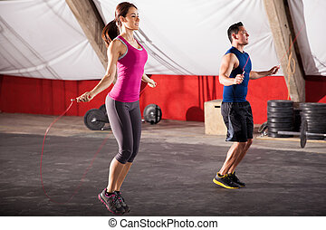 Exercising with a jump rope - Young man and woman jumping...