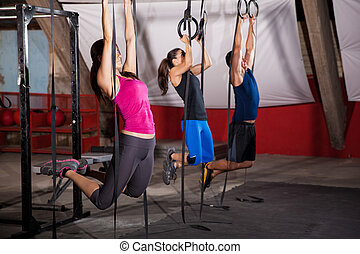 Doing the WOD for crossfit - Group of three people pulling...