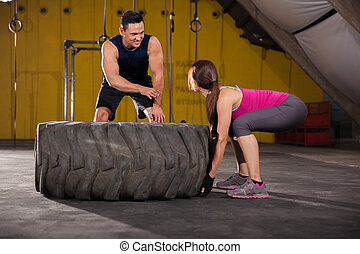Giving advice on tire flip - Athletic young woman getting...